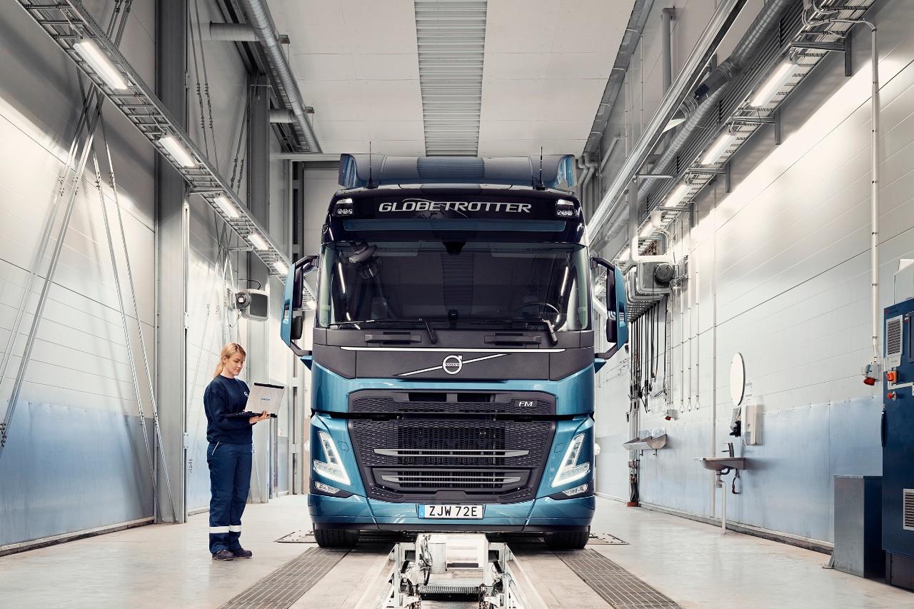 Volvo 服務技師手持電腦站在貨車旁