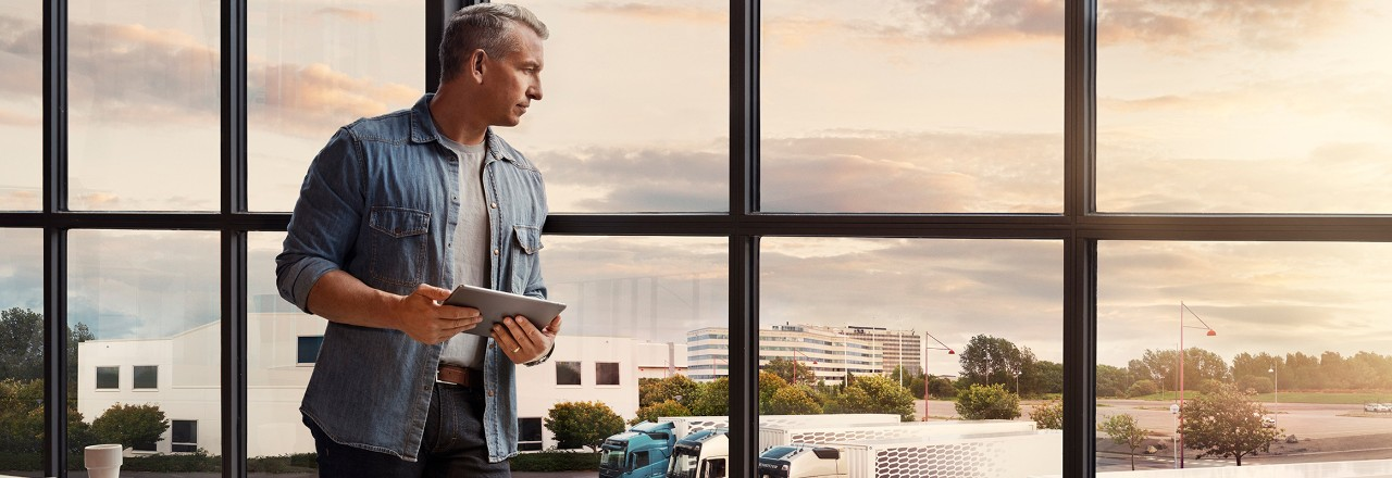 一個人拿著平板電腦站在窗邊,俯瞰他的卡車車隊